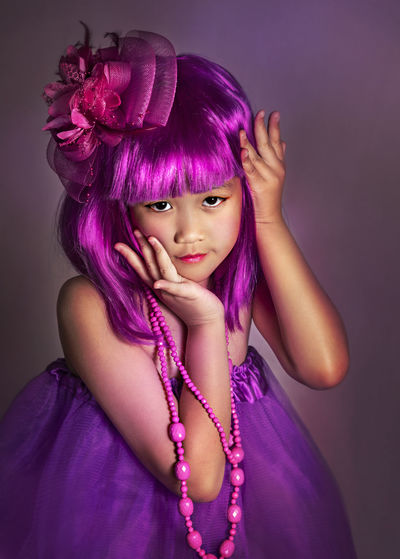 Portrait of cute girl standing against purple background