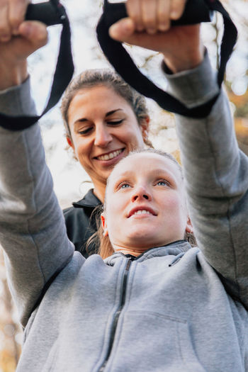 Low angle view of smiling women exercising in park