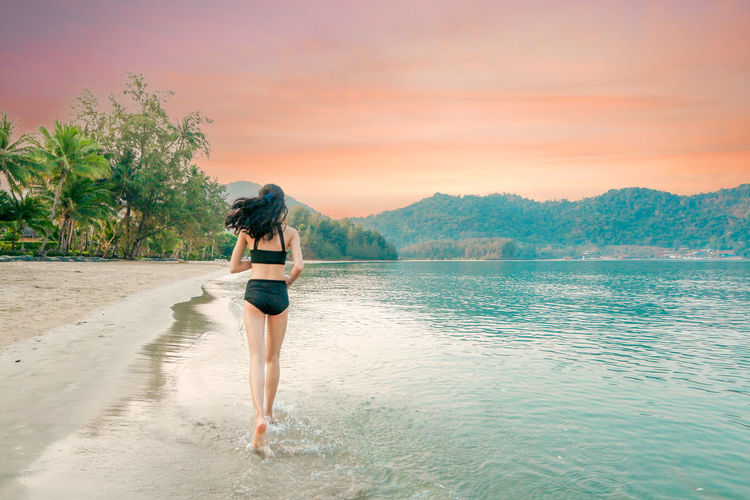 Rear view of woman standing in sea against sky during sunset