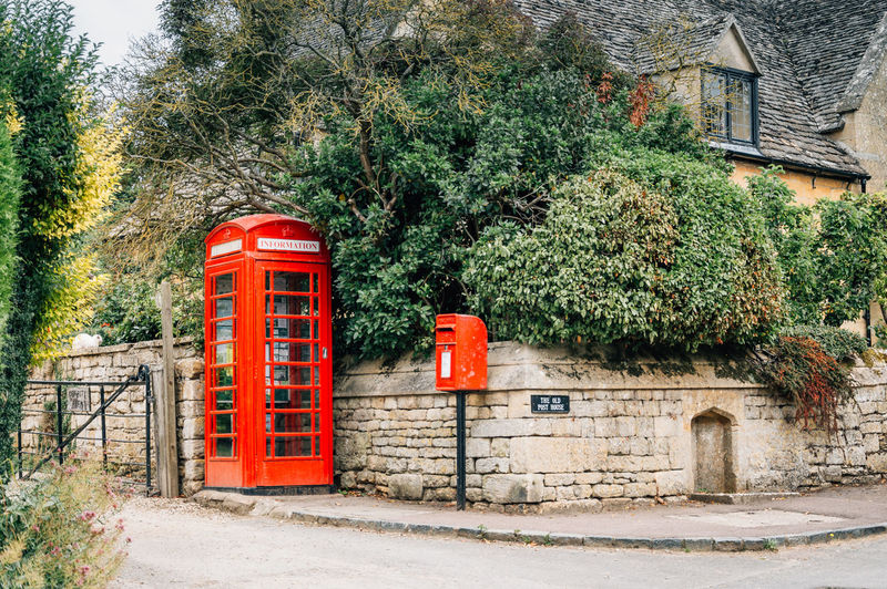 Corner in the village of Stanton with a red telephone box and a red mail Architecture Booth Box Building Exterior Built Structure Closed Cor Day Exterior Façade Green Color Growth Mailbox Nature No People Outdoors Plant Quaint  Red Sky Stanton  Street Telephone Travel Tree