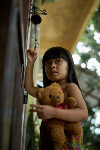 Low angle view of girl holding teddy bear standing at entrance