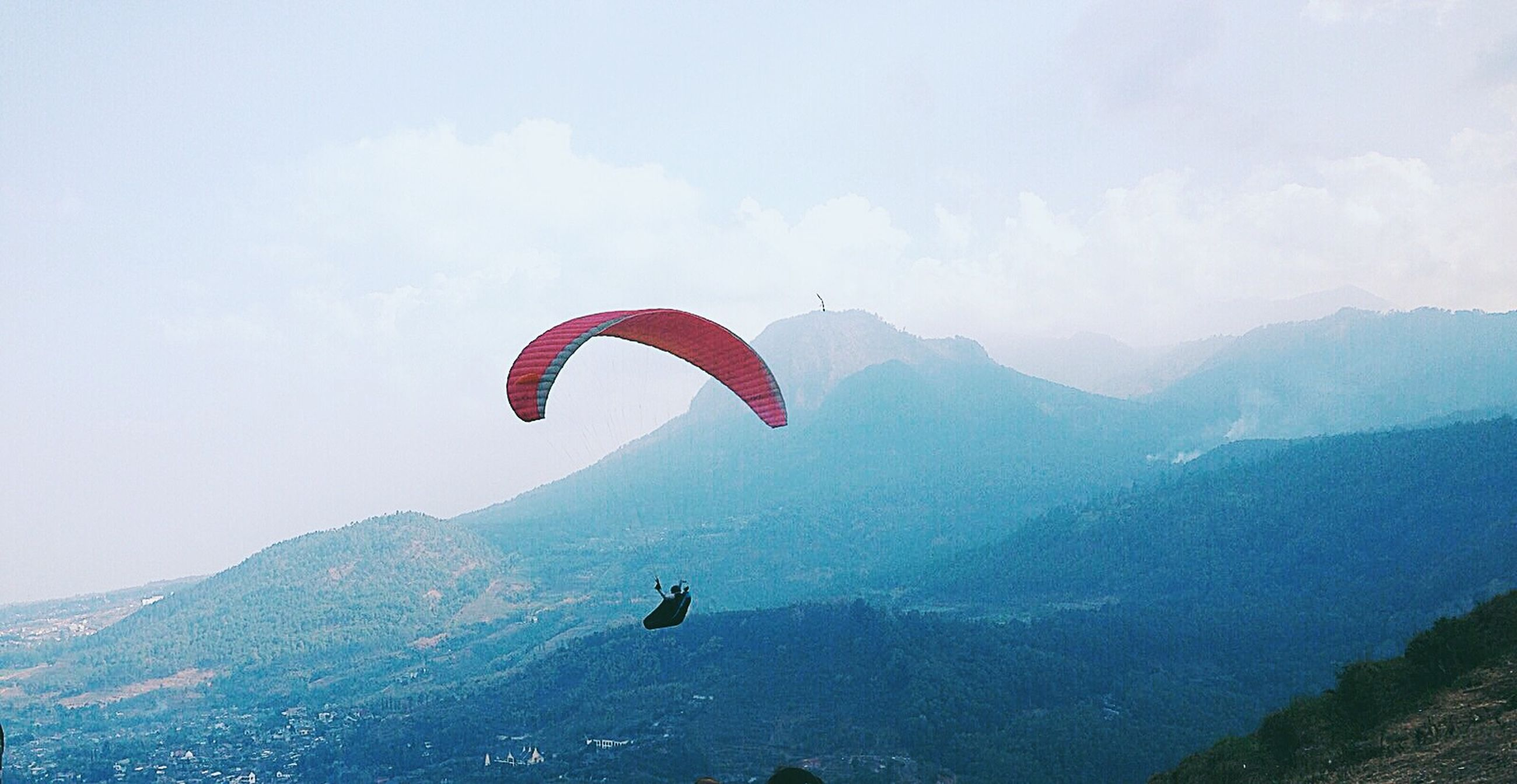 extreme sports, adventure, mid-air, parachute, mountain, leisure activity, paragliding, flying, lifestyles, sport, exhilaration, freedom, unrecognizable person, sky, low angle view, mountain range, transportation, vacations