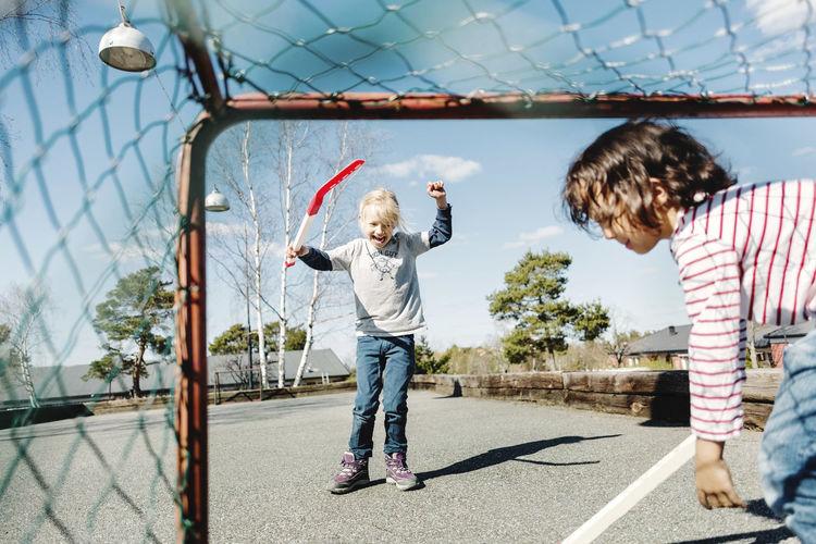 Full length of boys playing on soccer field against sky