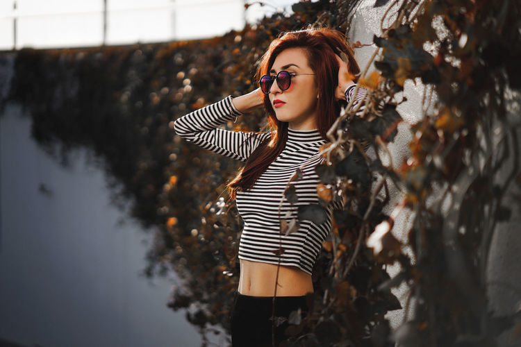 Young woman wearing sunglasses while standing by wall