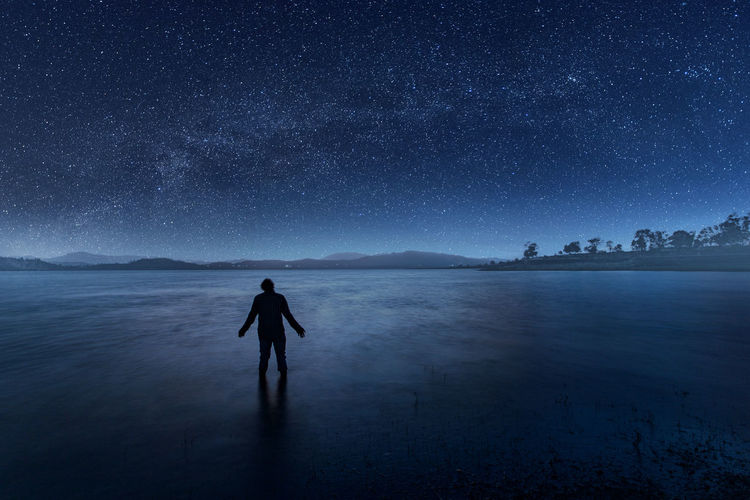 Rear view of man standing on land against sky at night