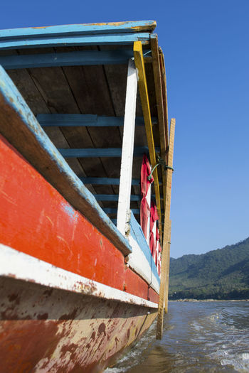 Close-up of a wooden river boat on the river mekong in south-east asia. slow travel and tourism.