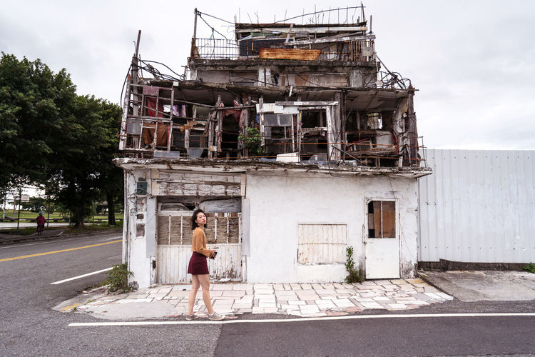 Woman walking on road by building against sky