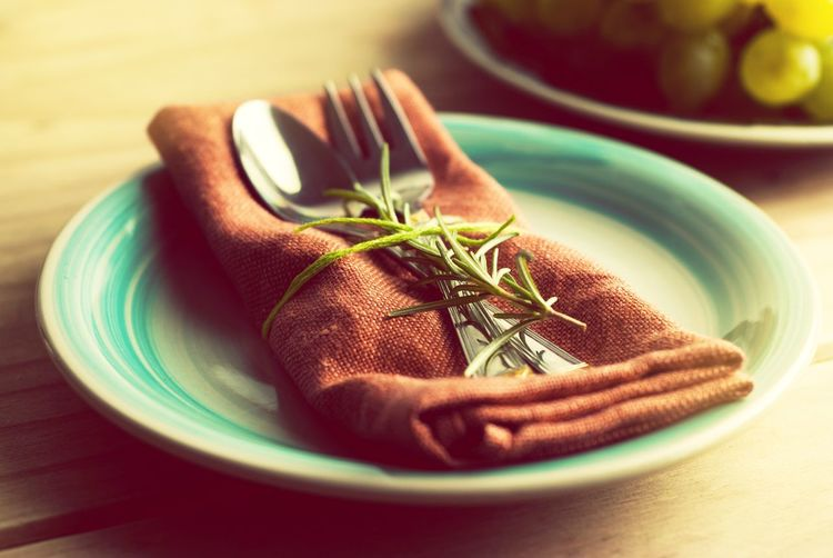 Close-up of silverware with napkin and rosemary in plate on table