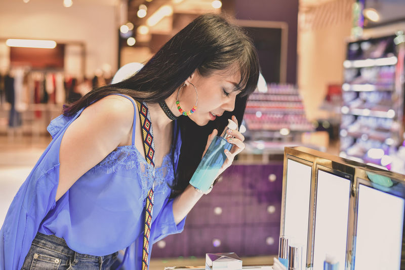 Young woman smelling perfume in store