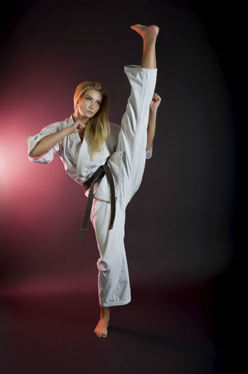 Full Length Of Flexible Woman Practicing Karate
