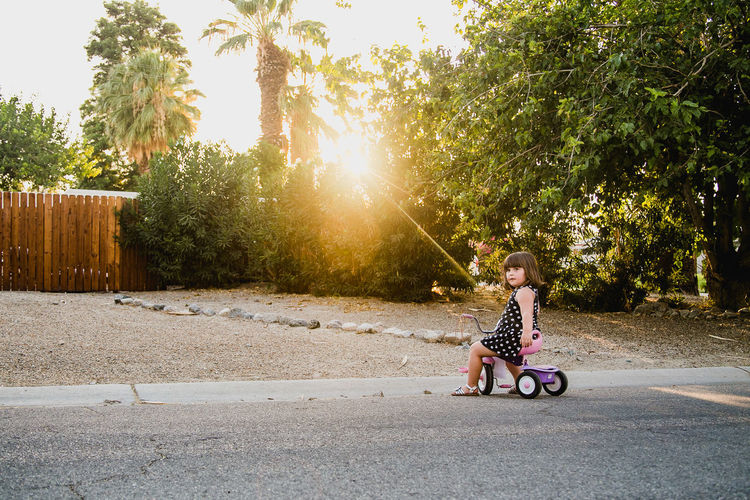 Side View Of Girl Riding Tricycle On Road