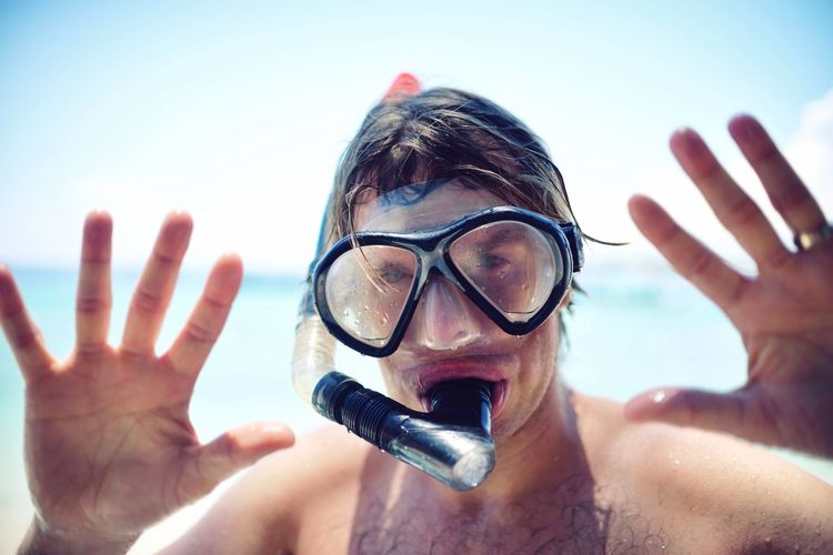 Close-up portrait of mid adult man wearing snorkel mask standing at beach against sky