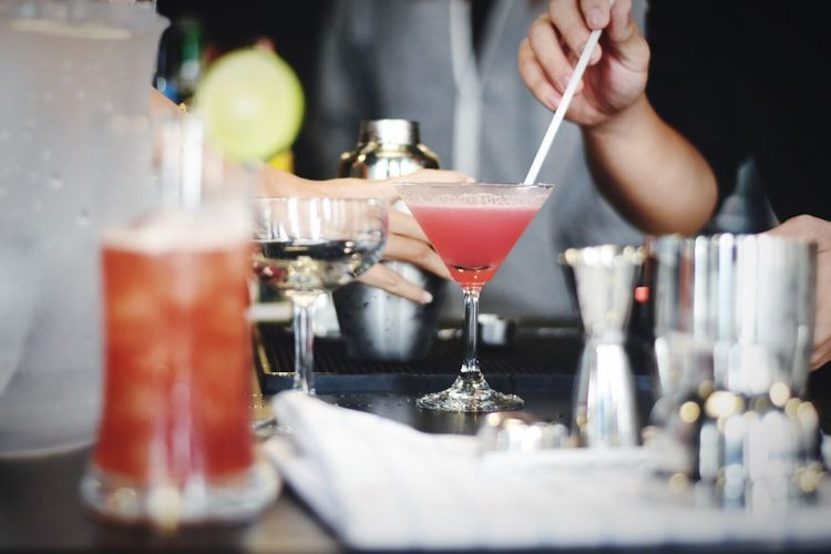 Cropped image of men with drink at bar counter