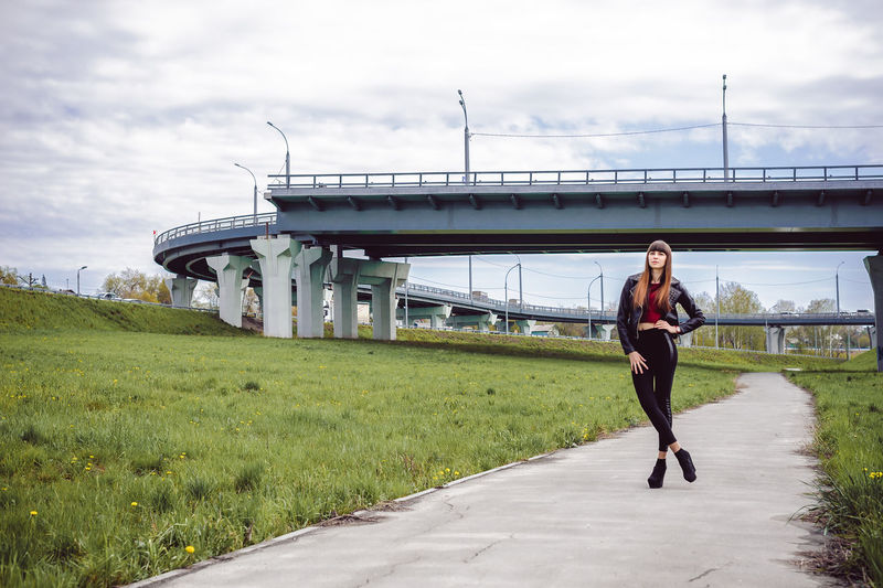 Full length portrait of fashionable young woman standing on footpath amidst field with bridge in background