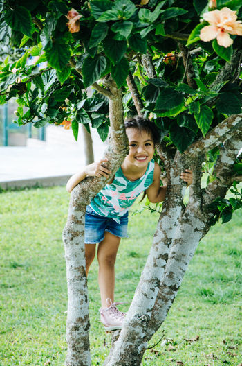 Portrait of girl smiling while standing on tree at park