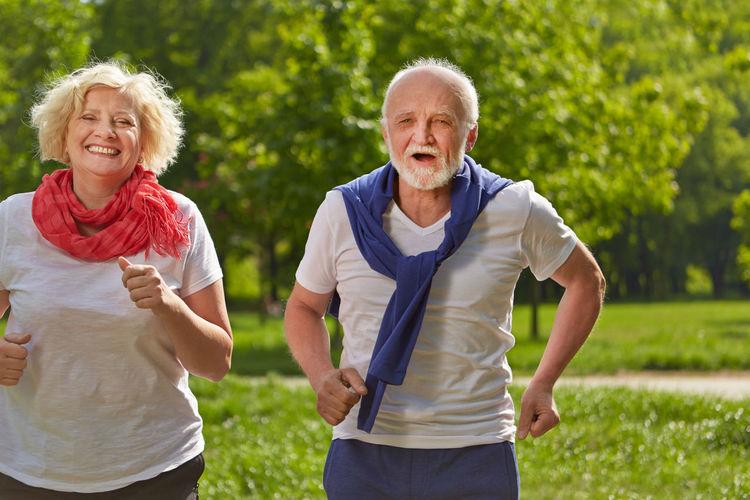Smiling Senior Couple Running At Park