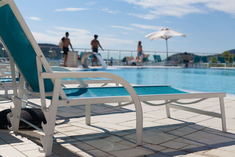 Empty chair at poolside against sky during sunny day