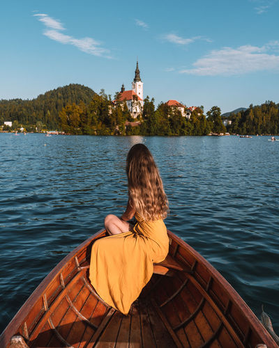 Side view of woman sitting on boat in lake