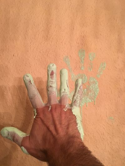 Man with paint on hand against wall