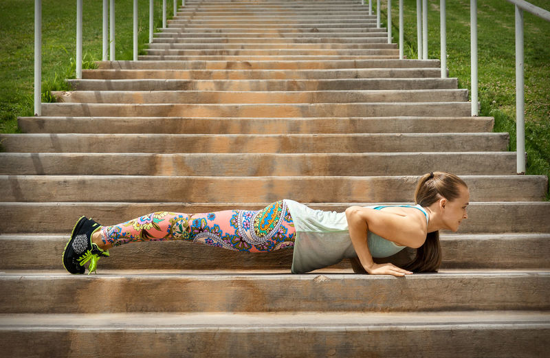 Active Woman Practicing Yoga Doing Plank Pose, Exercising Outdoor Body & Fitness Horizontal Sunlight Woman Yoda Adult Body Care Candid Effort Exercising Fit Healthy Lifestyle Lifestyles Muscles One Person Outdoors Outside Plank Pose Practicing Sport Staircase Strength Summer Young Adult