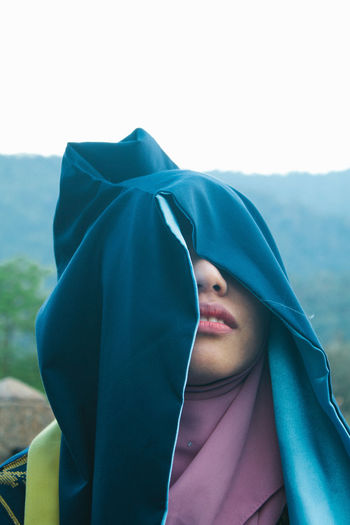 Beautiful young woman with covered face standing against sky outdoors