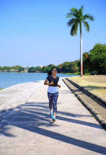Full length of woman jogging on footpath by lake against sky