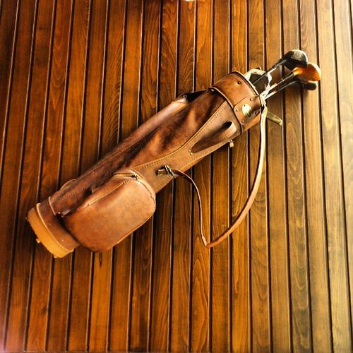 Nice Vintage Leather Golf bag with clubs in it hang on the wall at tgifridays fridays, taken by my sonyericsson sony xperia arc, medina madinah madina ksa saudi_arabia saudiarabia saudi arabia, جولف مطعم فرايديز المدينة_المنورة المدينة المنورة