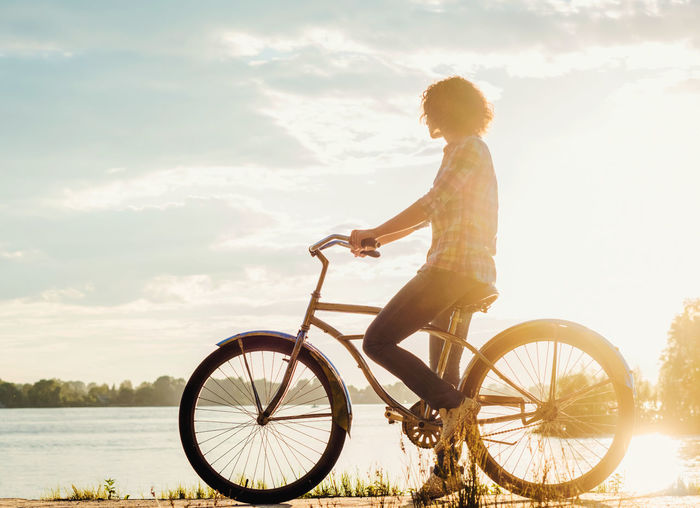 Side view of woman riding bicycle by lake against sky at sunset