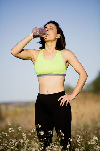 Girl drinking water wearing sporty clothes in the field Sporty Woman Sporty Girl Young Woman Crop Top Sportswear Field Runner Yoga Healty Fitness Attractive Sunset Sport Clothes Spring Summer Brunette Leggings Crop Tank Outdoors Lifestyles Exercising Recreational Pursuit Energy Nature Caucasian Athlete One Person Sky Land Front View Leisure Activity Healthy Lifestyle Young Adult Standing Three Quarter Length Women Day Plant Clear Sky Real People Clothing Sports Clothing Young Women