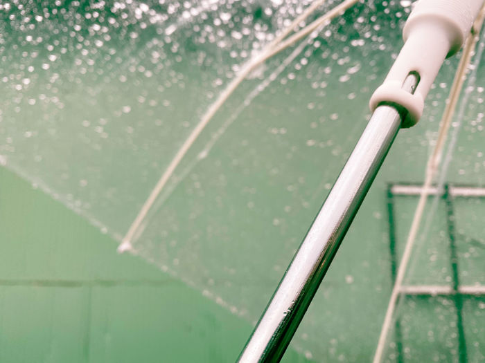 Close-up of water drops on umbrella against green wall