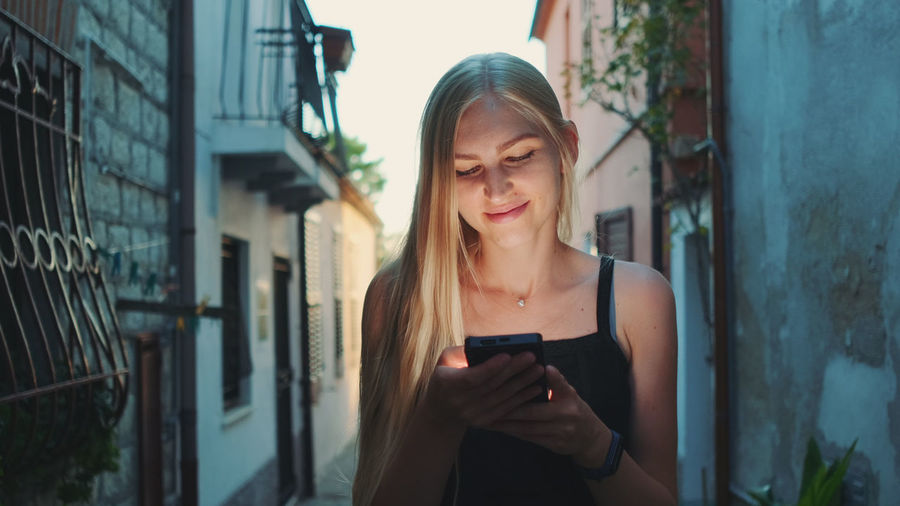 Young woman using smart phone while standing amidst buildings