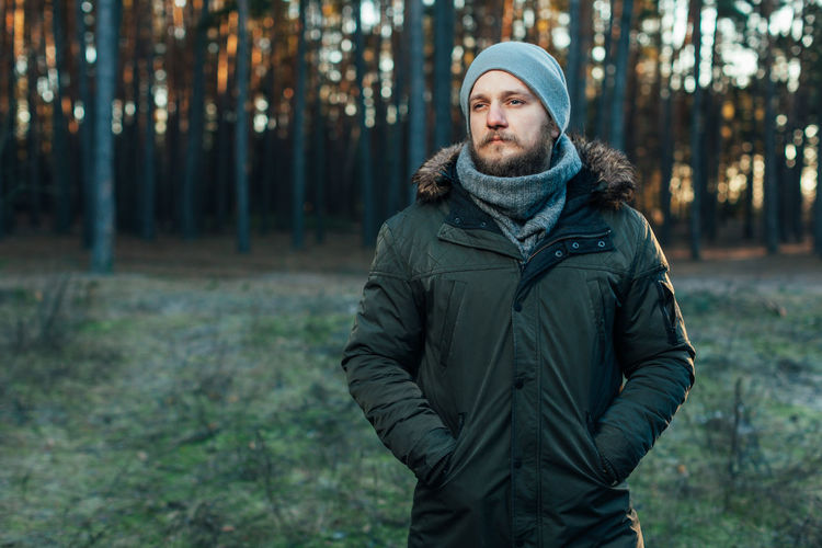 brutal bearded man in the autumn forest Beard Clothing Cold Temperature Forest Hat Hood - Clothing Jacket Land Looking At Camera Men Nature One Person Outdoors Plant Portrait Scarf Standing Tree Waist Up Warm Clothing Winter WoodLand Young Adult