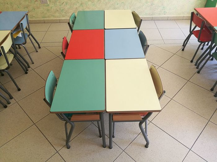 High angle view of tables and chairs on tiled floor in kindergarten