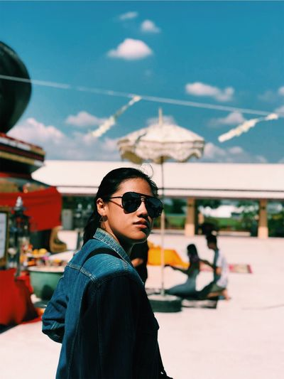 Portrait of woman wearing sunglasses standing against sky