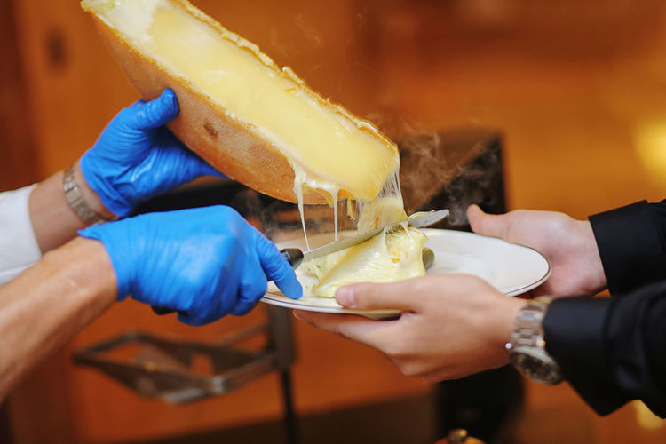 Cropped hands of cheesemonger serving cheese to customer in plate