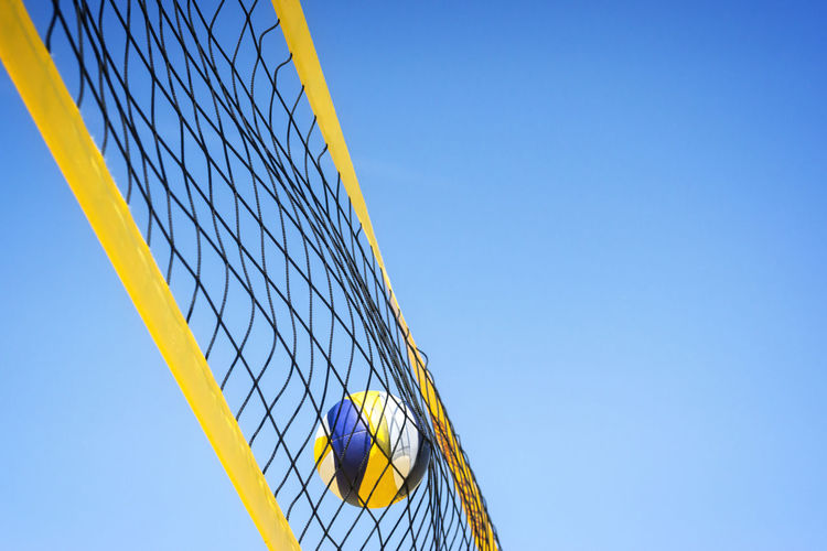 Beach volleyball caught in the net. Beach Volleyball Blue Clear Sky Day Low Angle View Net - Sports Equipment No People Outdoors Sky Sport Fresh On Market 2017