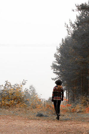 hiking and exploring by the lake Adult Adults Only Autumn Colors Beauty In Nature By The Lake Day Exploring Fall Beauty Foggy Day Full Length Girl Hat Hiking Into The Woods Nature Naturelovers One Person Outdoors People Real People Rear View Sky Tree Warm Clothing Winter