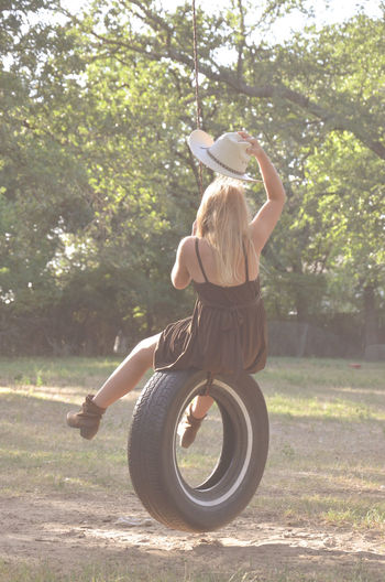 Rear view of woman sitting on tire swing at field