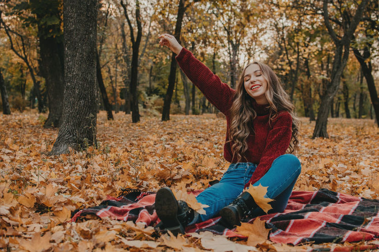 Smiling young woman sitting in forest during autumn