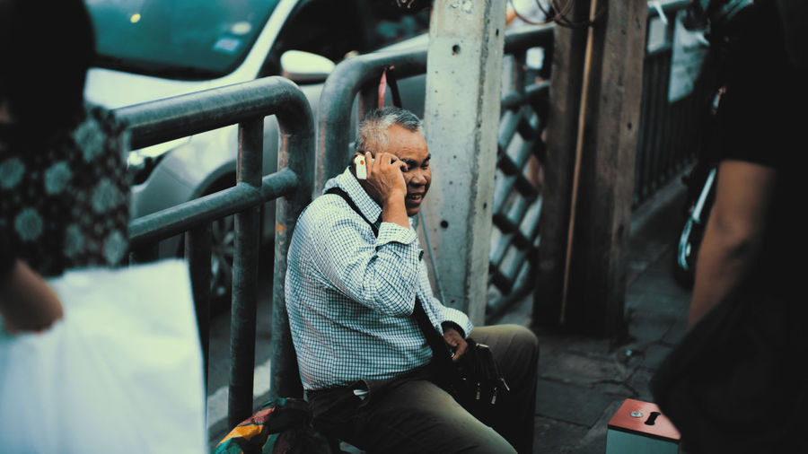 Man looking at camera while sitting on mobile phone