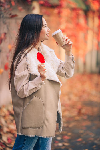 Side view of woman holding autumn leaves