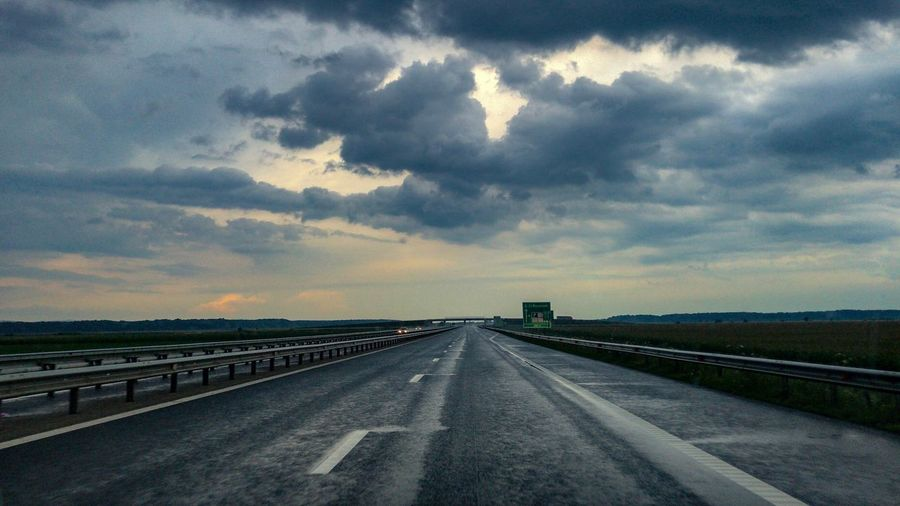 Rainy Days Cloud - Sky Sky Transportation Road Nature The Way Forward Diminishing Perspective Direction Highway No People vanishing point Landscape Environment City Dramatic Sky Sign Dusk Sunset Beauty In Nature Outdoors