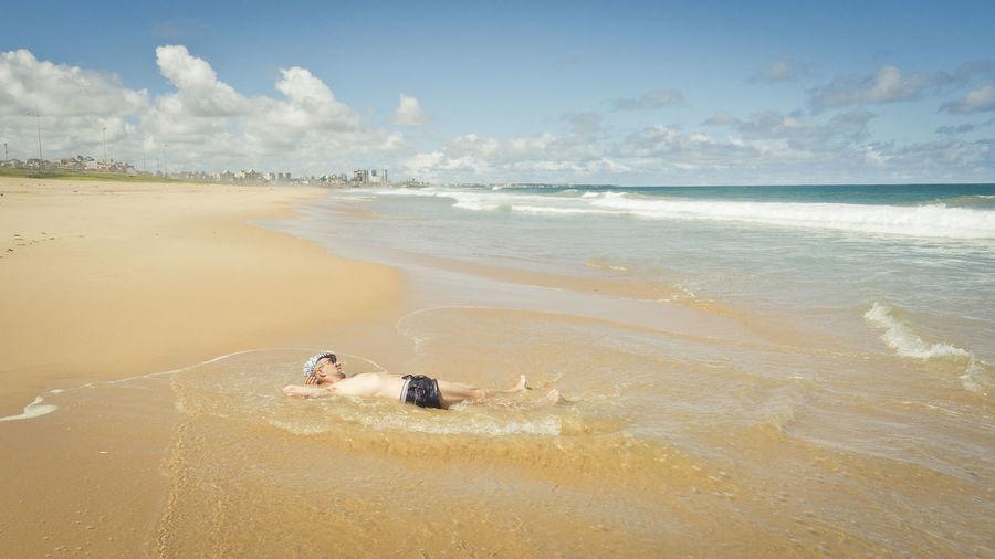 High angle view of man lying on beach