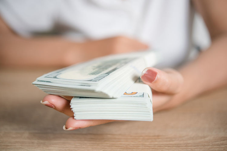 Midsection of businesswoman holding currency on table
