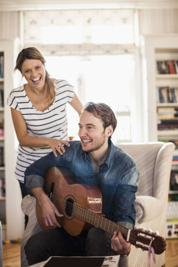 Happy young man playing guitar on sofa