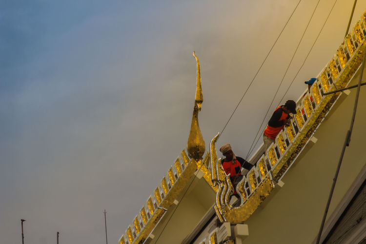 Chachoengsao, Thailand - May 12, 2017: Unidenitified workers during repair roof of the church in Wat Sothonwararam, a famous public temple in Chachoengsao Province, Thailand. Chachoengsao Chachoengsao Province Dramatic Sky Sothorn Wararam Worawiharn Temple WAT Sothon Wara RAM Worawihan (WAT Luang PHO Sothon) Wat Sothon Wat Sothon Wararam Worawihan Worker Worker And Tools Worker In Action Workers Architecture Building Exterior Built Structure Cable Cloud - Sky Day Dramatic Clouds Dramatic Light Dramatic Sunset Lifestyles Low Angle View Men Nature Occupation Outdoors People Public Temple Real People Repair Roof Rope Sky Sothon Sunset Wat Sothonwararam Worker At Work Worker Life Worker Tools Workers And Construction Workers Area Workers At Work Working
