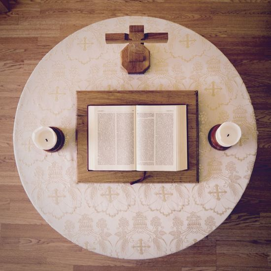 Top View Of Open Bible Book By Candles And Cross Shape On Wooden Table