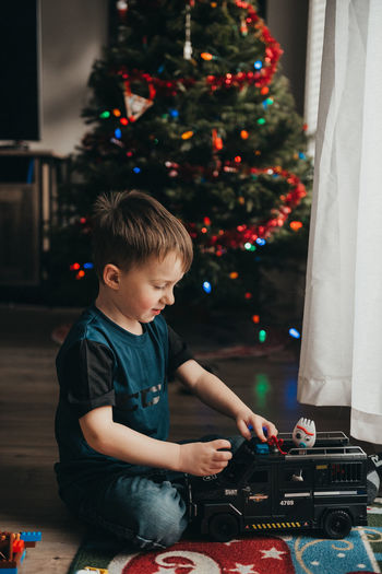 Full length of boy playing with toy against christmas tree at home