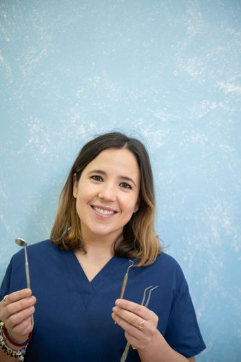 Portrait of smiling dentist holding medical equipment against wall