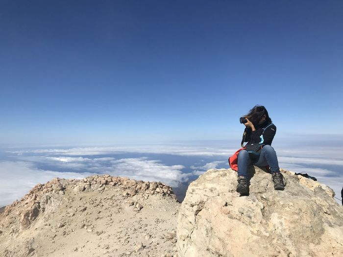 Woman sitting on rock against blue sky